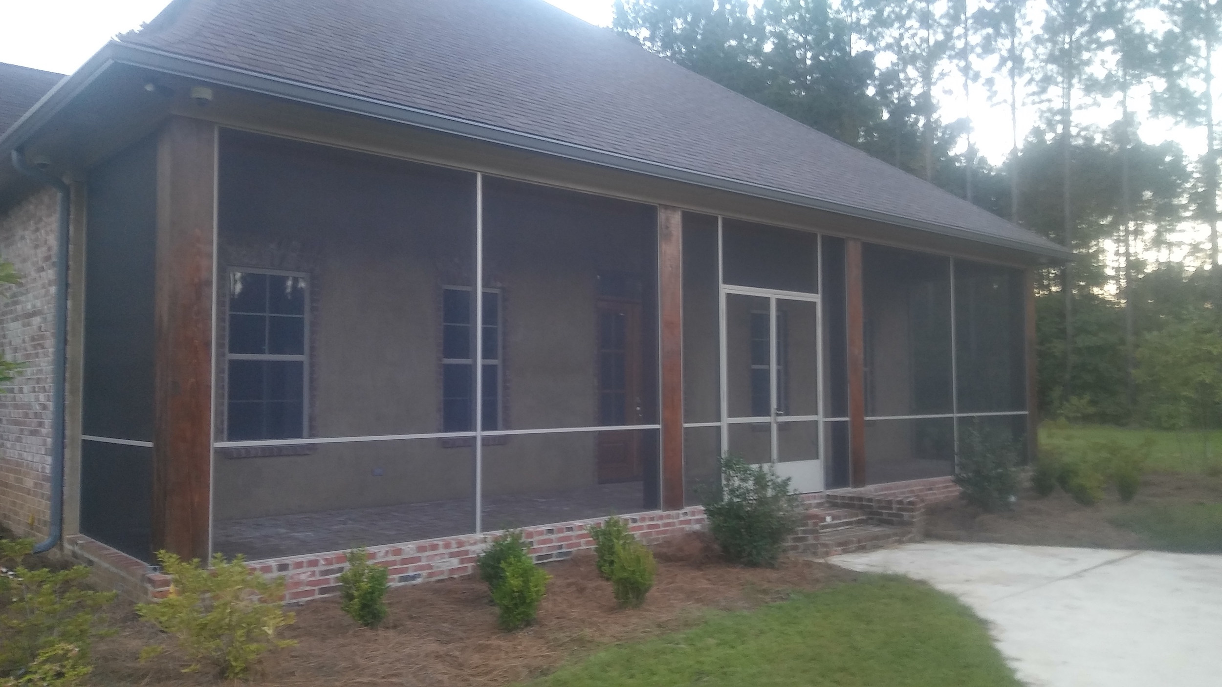 Screen porch added to the front of a house to create a bug-free living space outdoor.