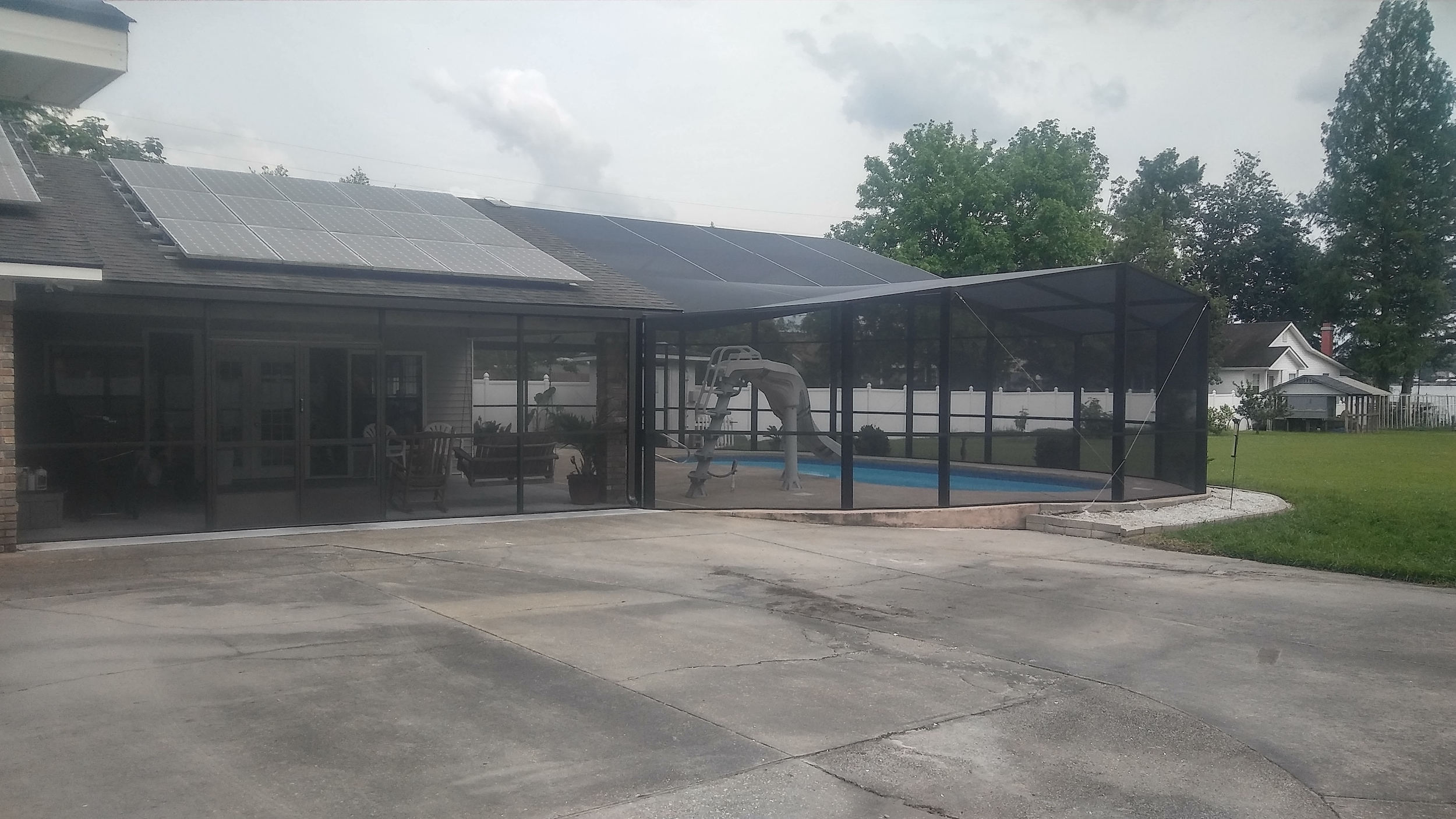 Affordable pool enclosure creating a covered outdoor living space for added pool safety and cleanliness.
